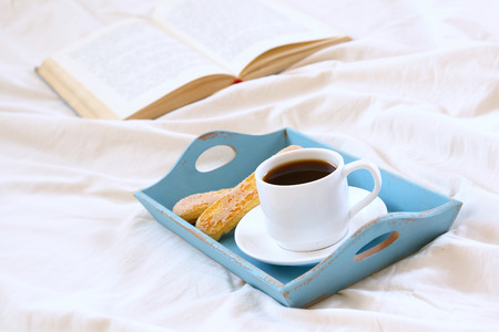 Romantic breakfast in the bed: cookies, hot coffees and open book