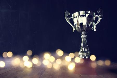 бизнес: низкий ключ изображения трофея над деревянным столом и темным фоном с абстрактными блестящими огнями