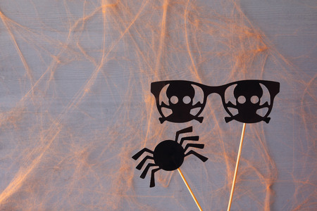funny glasses: Halloween holiday concept. Funny paper spider and pirate glasses.