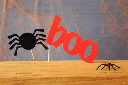 Halloween holiday concept. Paper funny spider and the word BOO. Stock Photo