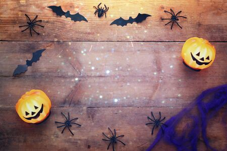 Halloween holiday concept top view. Pumpkins, spiders, bats on wooden old table