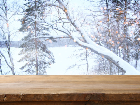 forest products: Empty wooden table in front of dreamy and magical winter landscape background. For product display montage