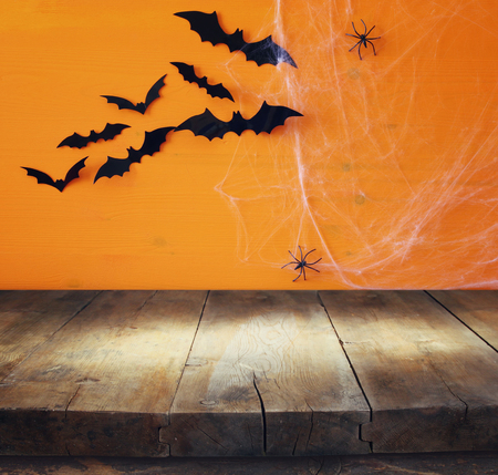 holiday display: Halloween holiday concept. Empty rustic table in front of spider web background. Ready for product display montage