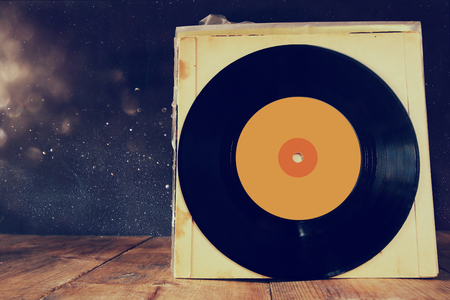 80 s: close up of old records on wooden table in front of glitter background. room for text