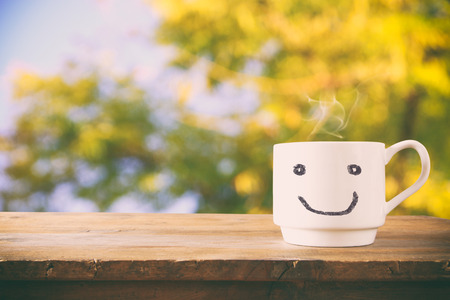 image of coffee cup with happy face over wooden table and tree leaves Stockfoto