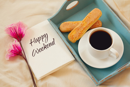 fin de semana: romántico desayuno en la cama: las galletas, café caliente, flores y una nota con el texto: Feliz fin de semana Foto de archivo