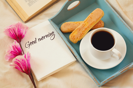 Romantic breakfast in the bed: cookies, hot coffee, flowers and note with the text: GOOD MORMING! Stock Photo
