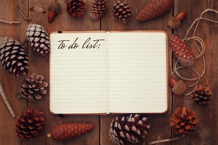 hacer: Vista superior de piñas y cuaderno abierto con el texto: Para hacer la lista, en el fondo de madera rústica. retro filtrada
