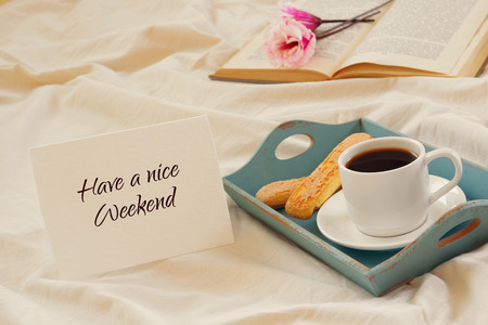 Romantic breakfast in the bed: cookies, hot coffee, flowers and note with the text: HAVE A NICE WEEKEND