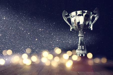 low key beeld van de trofee over houten tafel en donkere achtergrond, met abstracte glanzende lichten Stockfoto