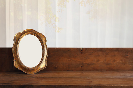 Golden old blank frame on wooden window sill.
