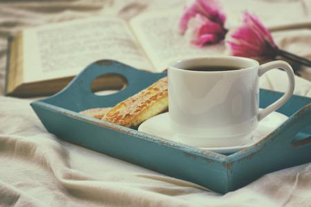 desayuno romantico: romántico desayuno en la cama: las galletas, café caliente y libro abierto. Retro filtrada y tonificado