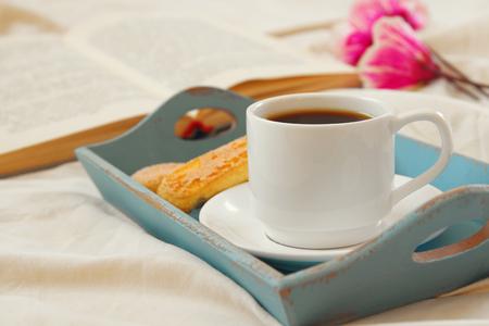 desayuno romantico: Romantic breakfast in the bed: cookies, hot coffee, flowers and open book. Foto de archivo