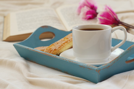 Romantic breakfast in the bed: cookies, hot coffee, flowers and open book. Stock Photo