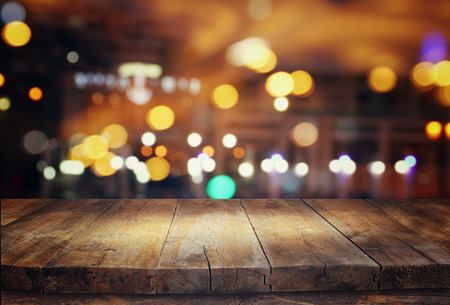 Image of wooden table in front of abstract blurred restaurant lights background Imagens