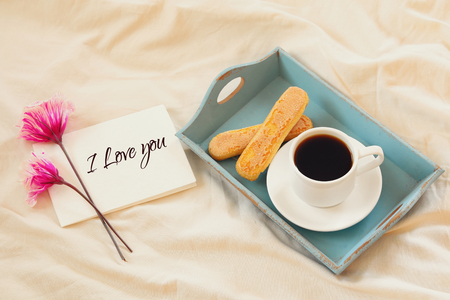 desayuno romantico: Romantic breakfast in the bed: cookies, hot coffee, flowers and note with the text: I LOVE YOU