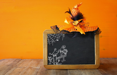 wooden hat: Halloween holiday concept. Witch hat, and blackboard on wooden table Stock Photo