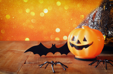 Halloween holiday concept. Cute pumpkin, spiders and bat on wooden table Stock Photo