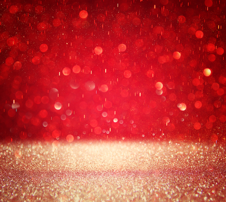 red glittery: red and silver defocused lights background.