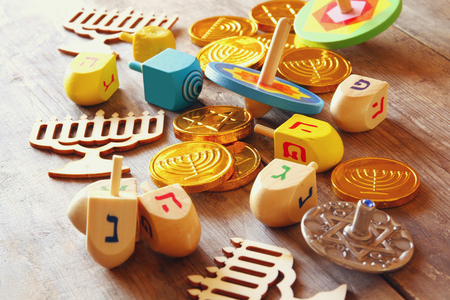 hanukka: Image of jewish holiday Hanukkah with wooden dreidels (spinning top) and coins chocolate on the table