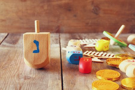 menora: Image of jewish holiday Hanukkah with wooden dreidels (spinning top) and coins chocolate on the table