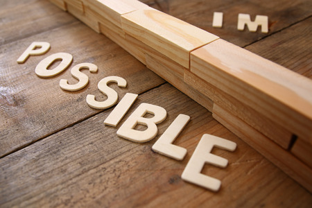 achievable: Image of the wall between of the letters IM from the word impossible so it says possible.