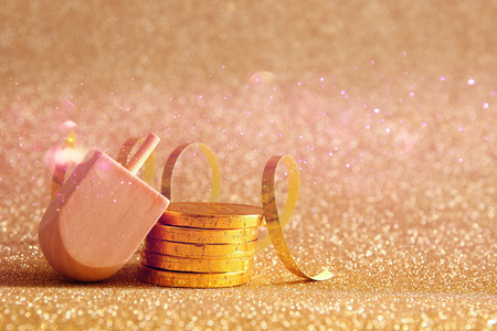 dreidel: Image of jewish holiday Hanukkah with wooden dreidel (spinning top) and chocolate coins on the glitter background Stock Photo