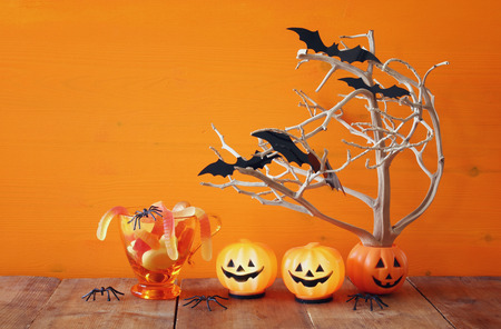 ghost house: Halloween holiday concept. Cute pumpkins, candy and tree with bats, on wooden table Stock Photo