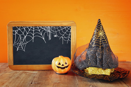 Halloween holiday concept. Witch hat, cute pumpkin next to blank blackboard