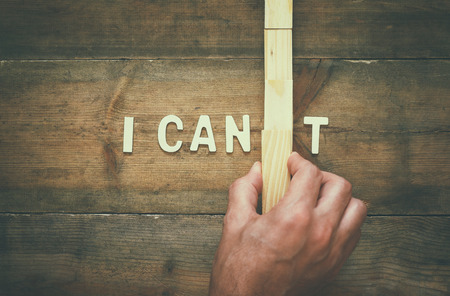 I T: Man hand building the wall between letters I CANT, cutting the letter T so it written I CAN. Success and challenge concept. retro style image