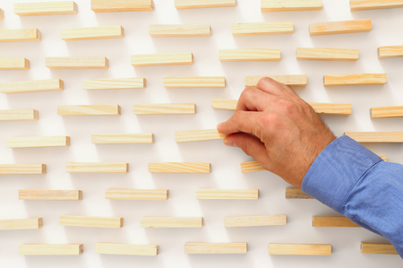 fragile economy: man hand pick one of wood block from many wooden blocks. top view over white background. business concept of choosing the right pick amongst other ones
