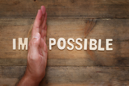 achievable: man hand dividing the letters IM from the word impossible so it says possible