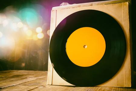 キラキラ背景の木製テーブルの上の古いレコードを閉じます。テキストのための部屋