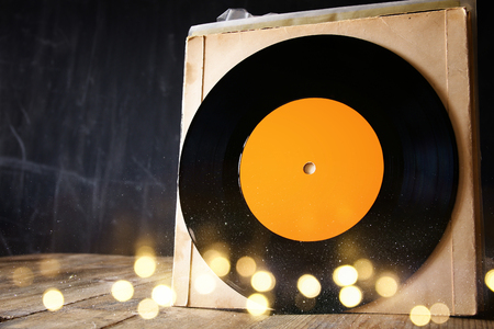 80 s: close up of old records on wooden table with glitter background. room for text
