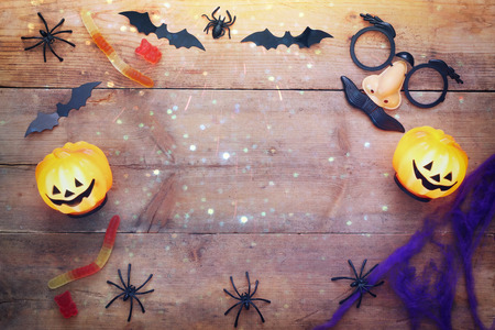 party hat: Halloween holiday concept top view. Pumpkins, spiders, witch hat, mask on wooden old table. Glitter overlay