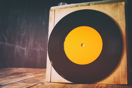 80 s: close up of old records on wooden table. room for text. retro filtered and toned