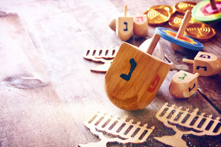 hanuka: Image of jewish holiday Hanukkah with wooden dreidels colection (spinning top) and chocolate coins on the table. Glitter overlay