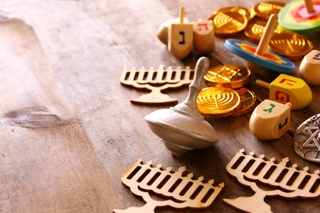 judaica: Image of jewish holiday Hanukkah with wooden dreidels colection (spinning top) and chocolate coins on the table