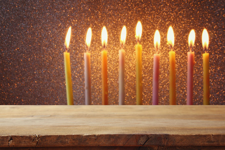 chanukkah: Empty wooden table in front of jewish holiday Hanukkah background with menorah (traditional candelabra) and burning candles Stock Photo