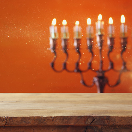 Empty wooden table in front of jewish holiday Hanukkah background with menorah (traditional candelabra) and burning candles Stock Photo