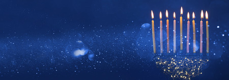 hanukka: Low key Image of jewish holiday Hanukkah background with menorah (traditional candelabra) and burning candles. Glitter overlay. Wide format Stock Photo