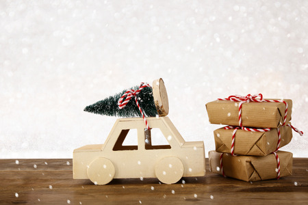 Wooden car carrying a christmas tree in front of glitter background