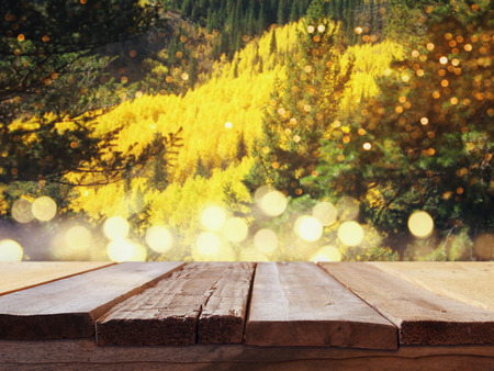 forest products: Empty wooden table in front of autumnal landscape background with glitter lights. For product display montage