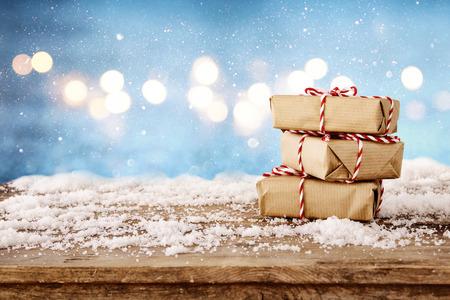 Imagen de cajas de regalo hecho a mano sobre la mesa de madera cubierto de nieve