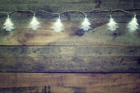 christmas light: image of Christmas tree garland lights on wooden rustic background Stock Photo