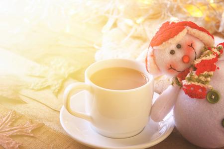 cioccolato natale: Tazza bianca con cioccolata calda, pupazzo di neve e luci di Natale.