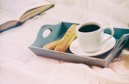 desayuno romantico: Image of romantic breakfast in the bed: cookies, hot coffee and open book