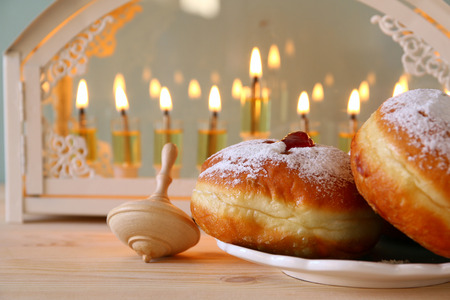 Selective focus image of jewish holiday Hanukkah with menorah (traditional Candelabra), donuts and wooden dreidel (spinning top) Stock Photo