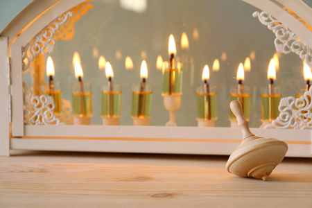 Selective focus image of jewish holiday Hanukkah with menorah (traditional Candelabra) and wooden dreidel (spinning top) Stock Photo