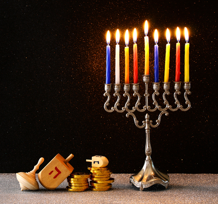 low key image of jewish holiday Hanukkah with menorah (traditional Candelabra) and wooden dreidels (spinning top). retro filtered image